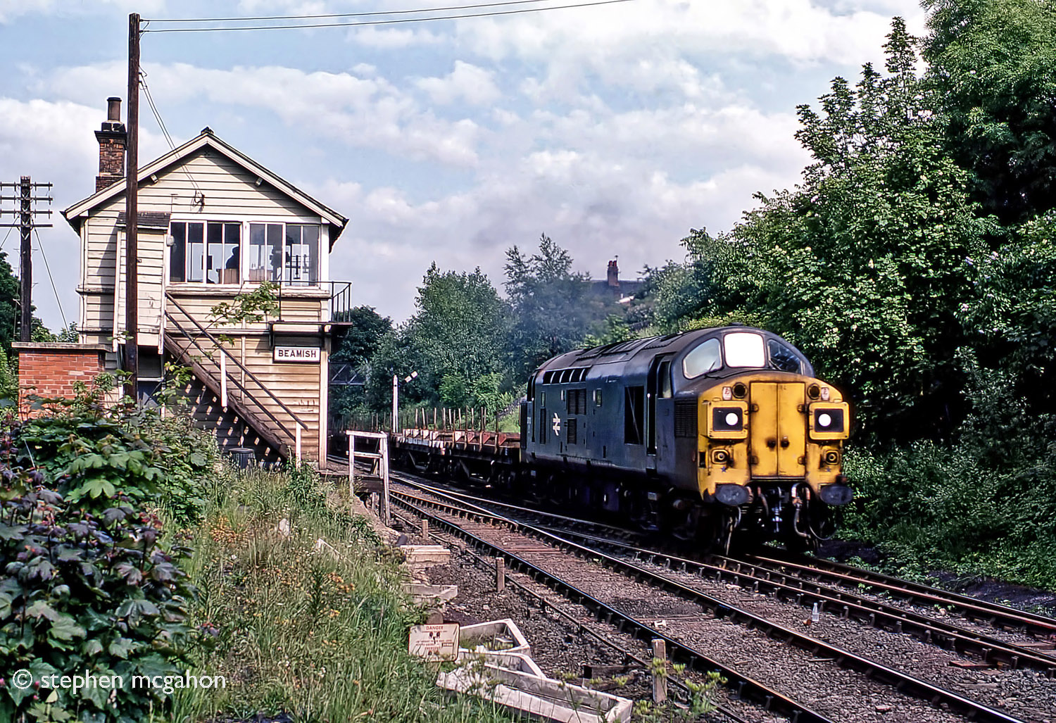 37113 working hard on the 1 in 50 bank past Beamish box with empty steel bolsters for Consett steelworks on 20th June 1978. The gradient eased here to 1 in 264 for a short distance through the site of Beamish station before resuming at 1 in 50, with even a stretch of 1 in 35, as far as Annfield Plain where the climb became less taxing for the last few miles to Consett. Photo copyright Stephen McGahon