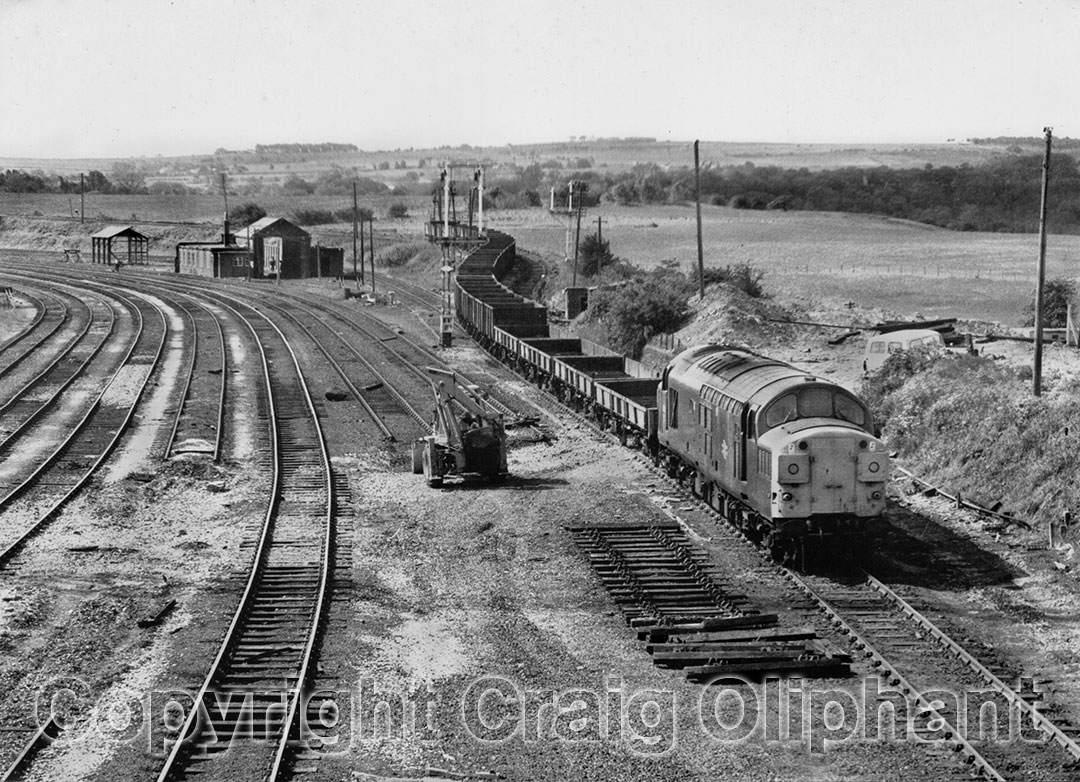 37079 in almost ex-works condition enters Consett Low Yard from the High Yard, with a train of empties for recovery of track materials and steel works scrap in August 1983. The remains of Consett Shed is seen to the left of the rear of the train. Photo copyright Craig Oliphant