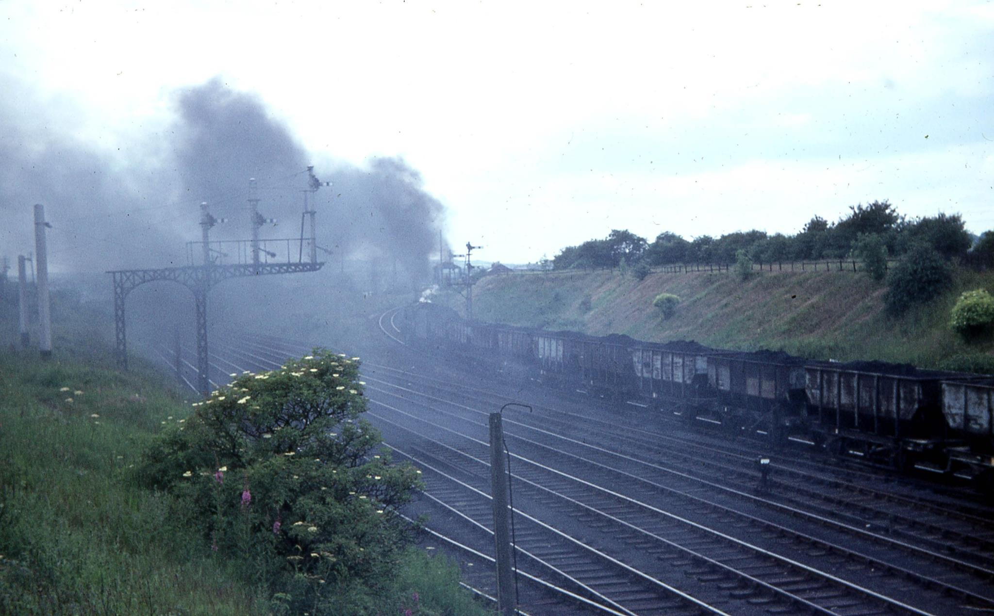 9F 92099 heads up the bank past Stella Gill with a train of 21T coal hoppers for Consett.