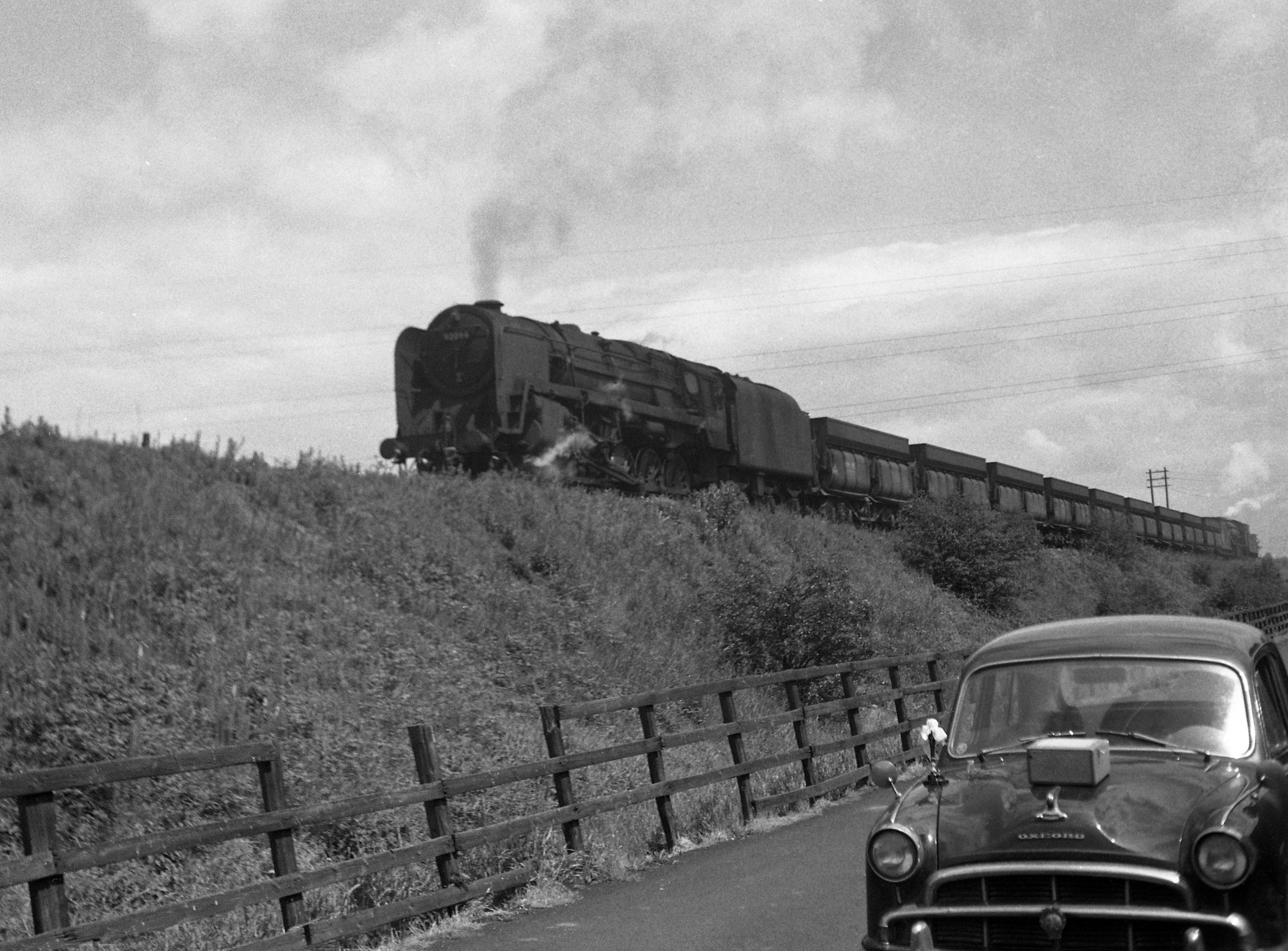 92063 pounds up the hill at Stanley with a loaded iron ore train in 1963. The train is being banked by a WD.