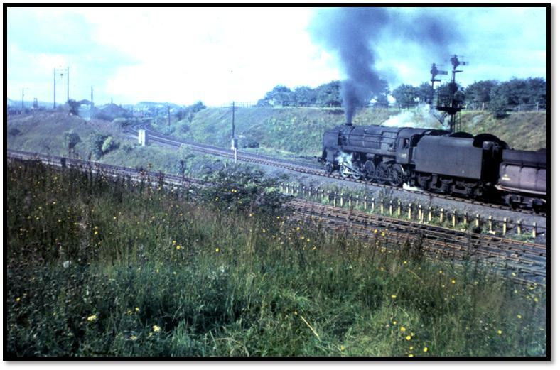 The steep gradient of 1 in 36 can be seen clearly in this photo of 92097 as it hauls its heavy train up the bank, blackening the sky in the process.