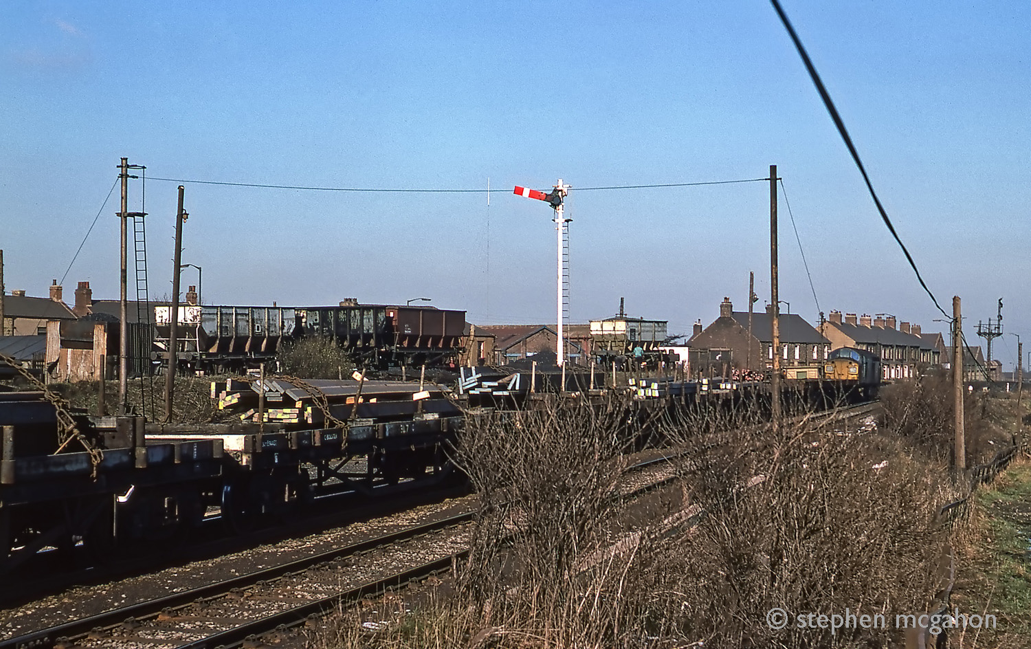37100 leaving Consett with a steel train on 28th February 1977. Taken near the site of Carr House East box which had gone by then as shown by the missing signal arms from the bracket signal in the background. I think the box would have been in the shot as well. Looks like a new starting signal in the centre and the coal drops in use adds a bit of interest. Caption and photo from Stephen McGahon