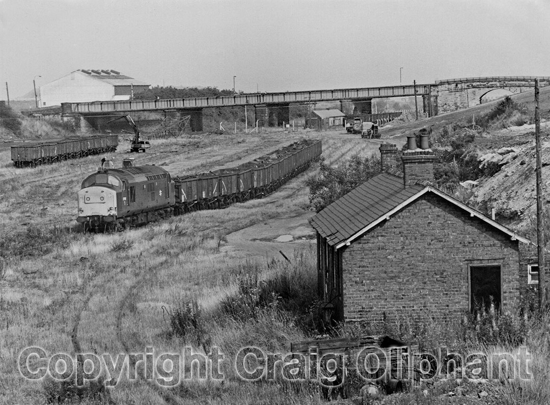 37198 in Consett Low Yard with a Scrap train consisting of parts of the steel works. Wagons above the loco are being loaded by a road crane, with a felled lighting pylon beyond, with wagons seen through the arch of the distant bridge. September 1983. Photo copyright Craig Oliphant