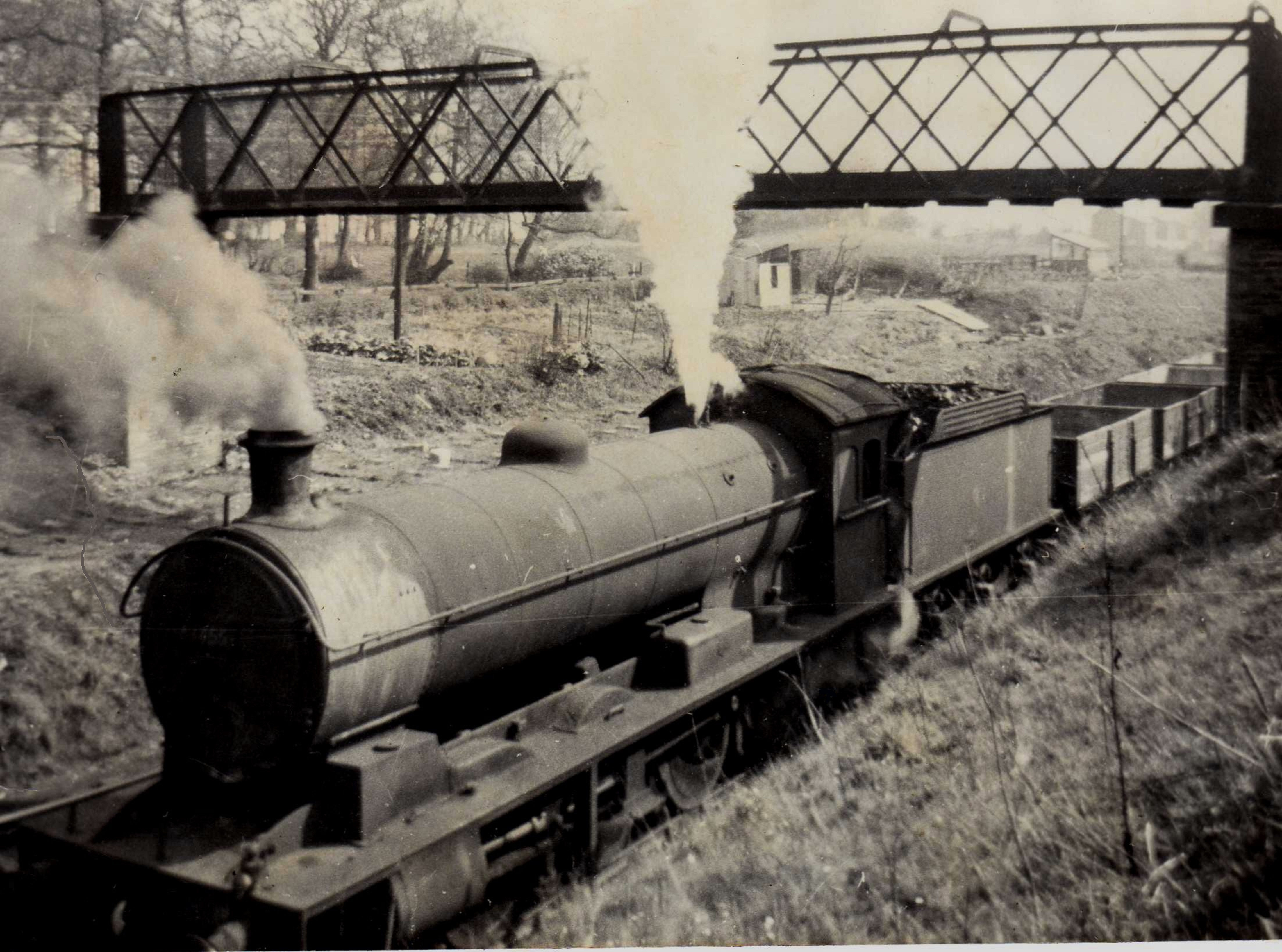 Q6 63455, with a trip working pauses at the Beamish home signal in the early 1960s. These trip wagons often contained little more than a smattering of scrap iron for the furnaces. In the background is Beamish's rickety footbridge, and through the April mist Thornton's Fold, a small row of miners' cottages. Note also the allotment, next to Beamish woods. This was well maintained as I remember, and its owner was in the process of building a shed. 63455 was a long term Consett engine and in that time honoured North Eastern tradition was sound rather than clean! Photo Copyright David Milburn