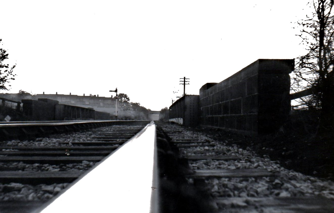 This rather unusual view, taken literally at rail level looks up past the Beamish distant signal to the station itself. In the foreground is overbridge 11 ( Stoney Lane) and in the distance bridge 12 which is still there today albeit with new decking. The terrace in the left distance is also there ( Nicholson Terr) but the community it led to over the bridge to the right (Thornton's Fold) disappeared 50 years ago. The grade here was I in 49 and it knocked the stuffing out of trains which had been picking up speed along Station Lane, Pelton. Photo Copyright David Milburn